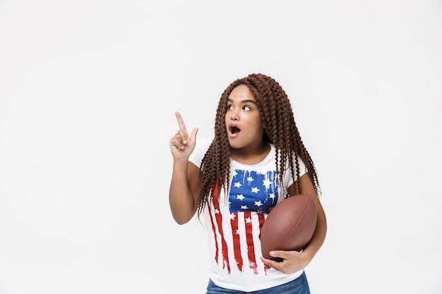 Portrait d'une femme excitée tenant un ballon de rugby pendant le match en se tenant isolé contre un mur blanc