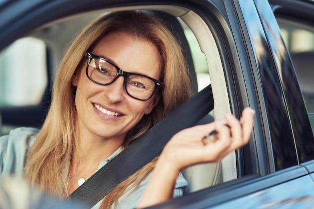 Portrait d'une femme excitée tenant des clés de voiture et souriant à la caméra alors qu'elle était assise derrière la direction
