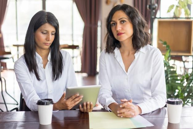 Portrait de femme exécutive sérieuse et sa secrétaire avec tablette numérique.