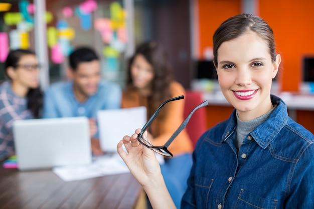 Portrait de femme exécutive souriante debout avec des lunettes
