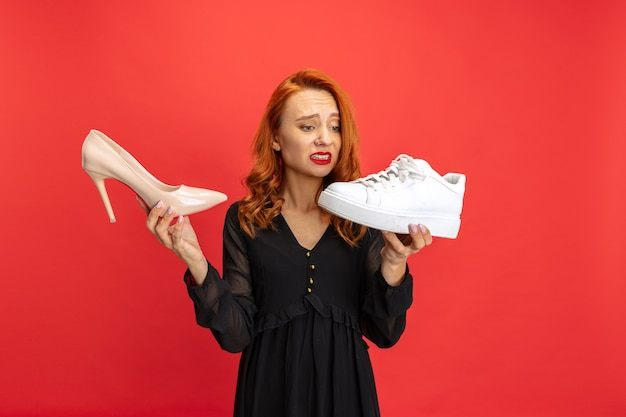 Portrait de femme expressive tenant des baskets et des chaussures à talons isolées sur le rouge
