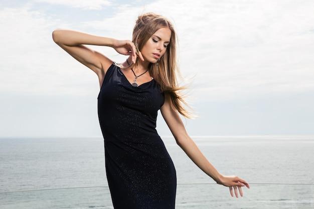 Portrait d'une femme fashion posant à l'extérieur avec la mer sur le mur