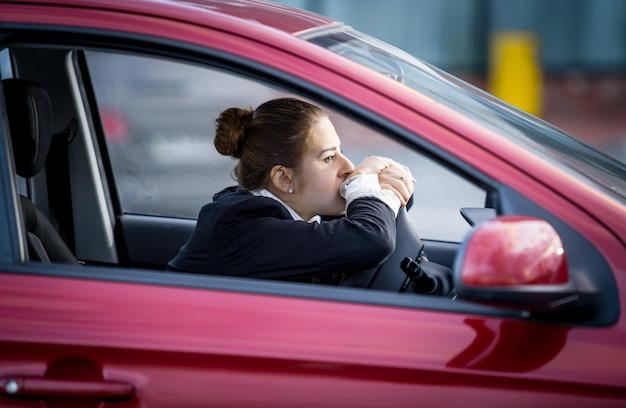 Portrait de femme fatiguée au volant d'une voiture et regardant par la fenêtre