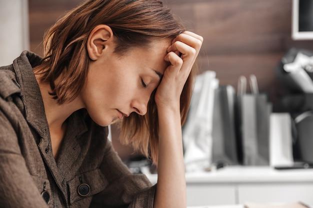 Portrait d'une femme fatiguée avec des maux de tête se bouchent