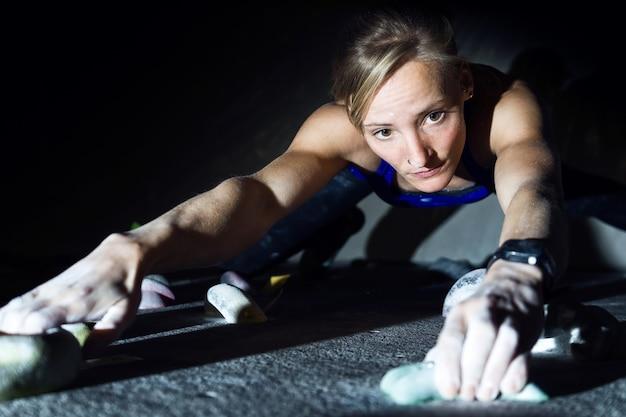 Portrait de femme fit l'escalade à l'intérieur de la salle de gym.