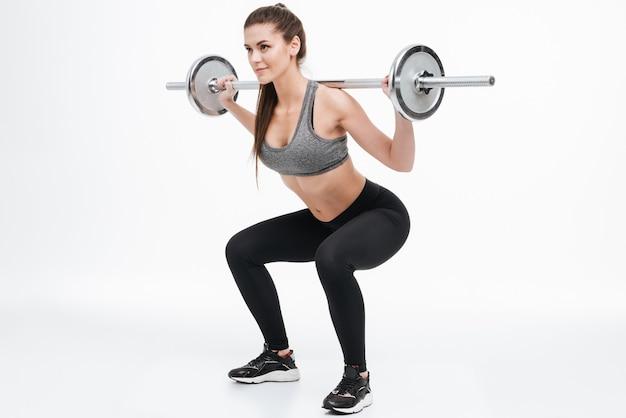 Portrait d'une femme fitness souriante ciblée faisant des squats avec haltères isolés