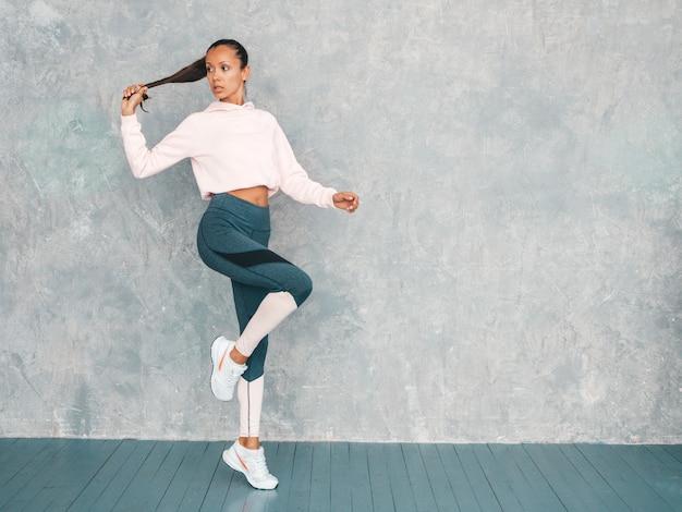 Portrait de femme fitness en vêtements de sport à la recherche de confiance. jeune femme portant des vêtements de sport. beau modèle avec un corps bronzé parfait. femme sautant en studio près du mur gris. tient en queue de cheveux à la main