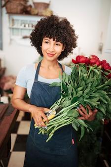Portrait d'une femme fleuriste souriante avec bouquet de fleurs rouges