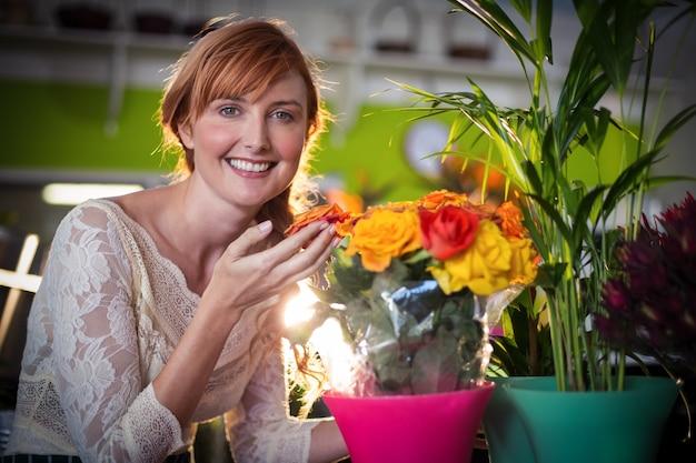 Portrait, femme, fleuriste, toucher, rose, fleurs