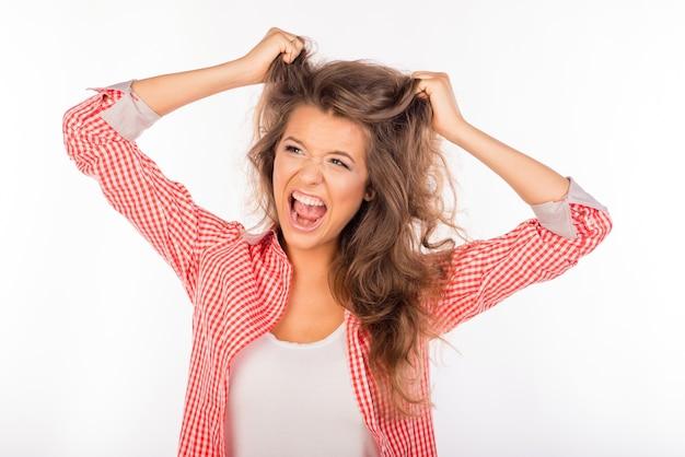 Portrait de femme folle criant et tenant les cheveux