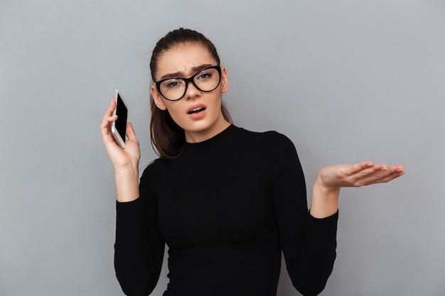 Portrait d'une femme frustrée confuse à lunettes
