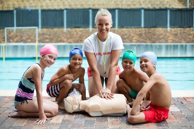 Portrait de femme gaie sauveteur et enfants pendant la formation de sauvetage