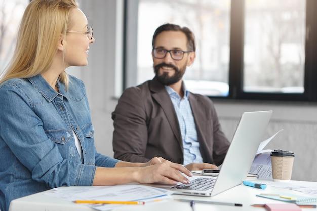 Portrait de femme gestionnaire et son patron travaillant ensemble au bureau