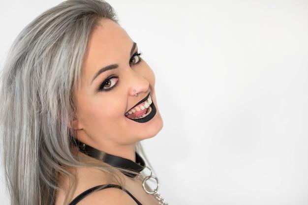 Portrait de femme gothique avec du maquillage fumé, souriant.