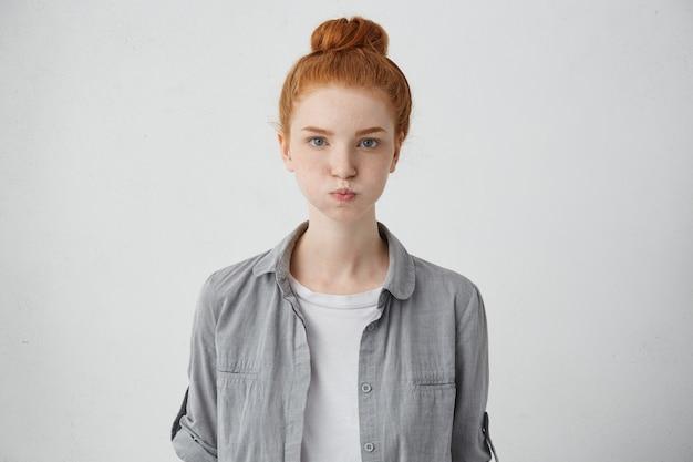 Portrait de femme grincheuse avec visage taché de rousseur, yeux bleus, cheveux roux et sourcils soufflant ses joues étant insatisfait de ses résultats. jolie fille rousse faisant la grimace ayant l'air bouleversé