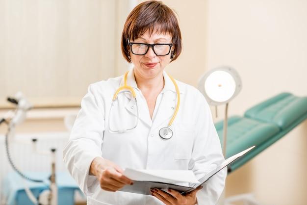 Portrait d'une femme gynécologue senior debout dans le bureau avec chaise gynécologique et lampe en arrière-plan