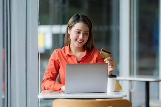 Portrait de femme heureuse à l'aide d'un ordinateur portable avec carte de crédit et visage souriant dans un bureau créatif ou un café au centre commercial
