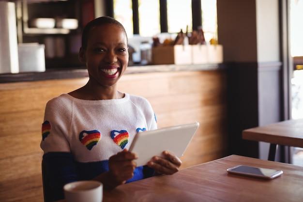 Portrait de femme heureuse à l'aide de tablette numérique