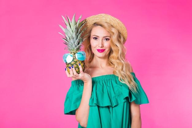 Portrait de femme heureuse et ananas sur fond rose. été, alimentation et mode de vie sain