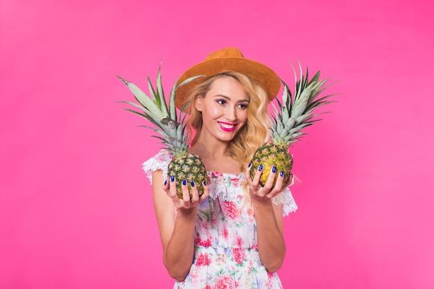 Portrait de femme heureuse et ananas sur mur rose. été, alimentation et mode de vie sain