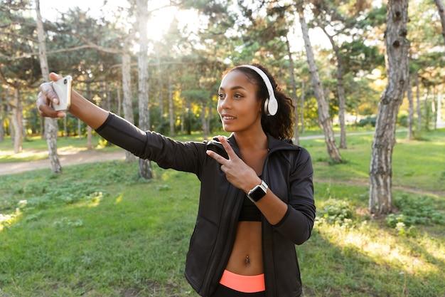 Portrait de femme heureuse des années 20 portant un survêtement noir et des écouteurs, prenant selfie photo sur téléphone portable tout en marchant dans le parc verdoyant