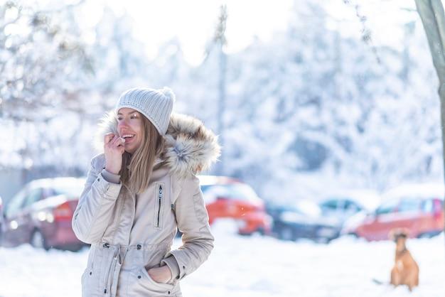 Portrait d'une femme heureuse appliquant un baume à lèvres en hiver