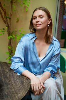 Portrait d'une femme heureuse assis à une table dans une chemise bleue dans un café