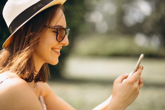 Portrait d'une femme heureuse au chapeau parlant au téléphone
