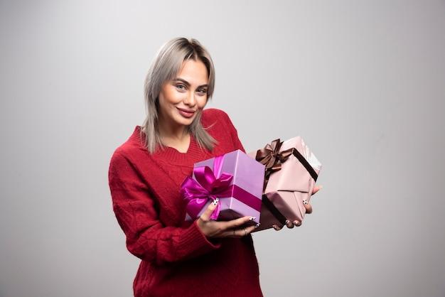 Portrait de femme heureuse avec des coffrets cadeaux posant.
