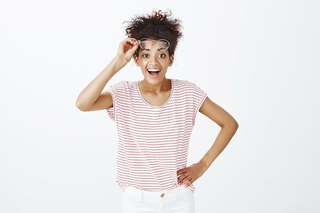 Portrait de femme heureuse avec une coiffure afro posant dans le studio