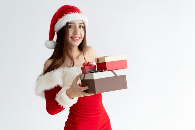 Portrait de femme heureuse en costume de père noël tenant des cadeaux de noël