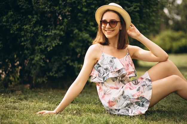 Portrait d'une femme heureuse dans un chapeau assis sur l'herbe