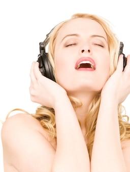 Portrait de femme heureuse dans les écouteurs sur mur blanc