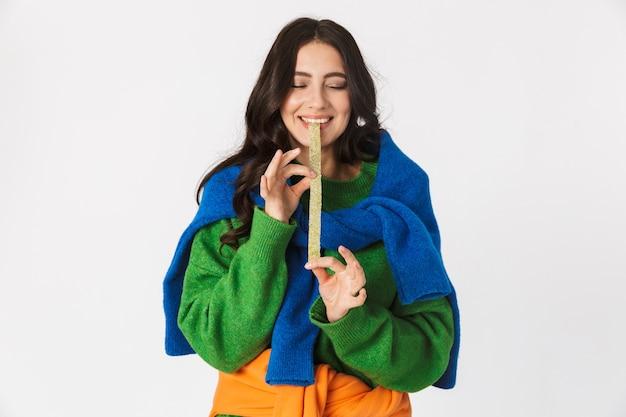 Portrait de femme heureuse dans des vêtements colorés à mâcher de la gomme longue, debout isolé sur blanc