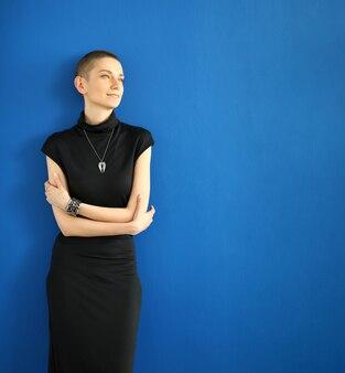 Portrait de femme heureuse en détournant les yeux avec joie et calme. femme réfléchie debout près du mur bleu. dame pensive en robe noire élégante