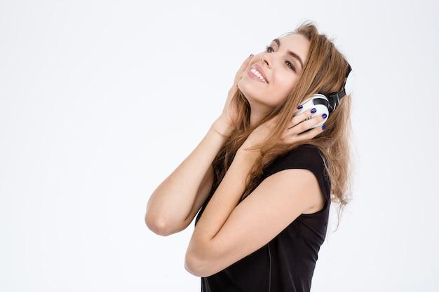 Portrait d'une femme heureuse écoutant de la musique dans un casque isolé sur fond blanc