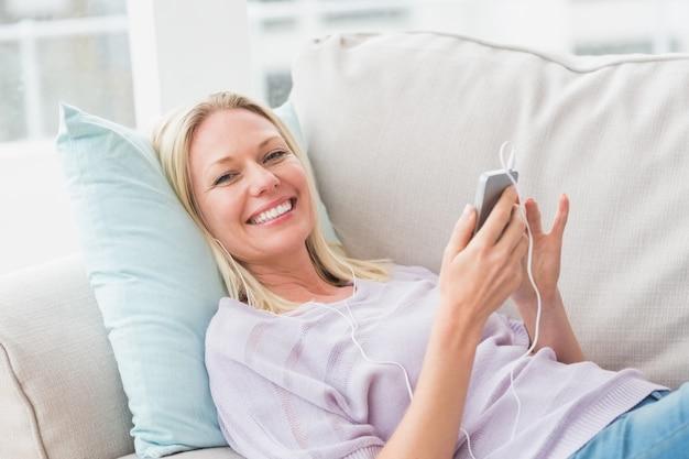 Portrait de femme heureuse, écouter de la musique par téléphone mobile en position couchée sur le canapé