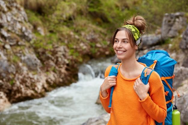 Portrait de femme heureuse extrême explorer sourit largement, pose avec sac à dos près du ruisseau
