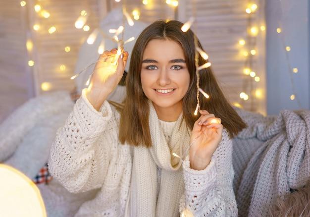 Portrait d'une femme heureuse avec des guirlandes en prévision des vacances du nouvel an