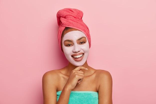 Portrait de femme heureuse heureuse avec masque d'argile du visage, incline la tête et touche le menton, enveloppé dans une serviette, se soucie de la beauté, sourit joyeusement et montre des dents blanches