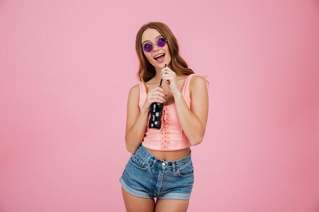 Portrait d'une femme heureuse en lunettes de soleil et vêtements d'été