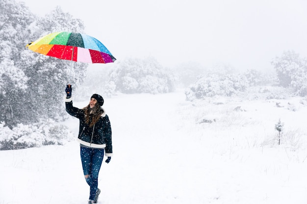 Portrait d'une femme heureuse marchant et tenant un parapluie coloré lors d'une chute de neige.