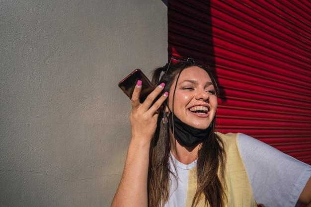 Portrait d'une femme heureuse avec un masque de protection parlant d'un smartphone