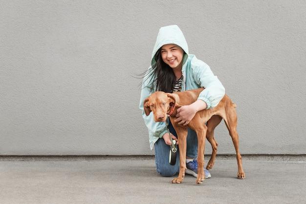 Portrait d'une femme heureuse avec un mignon chien brun contre un mur gris