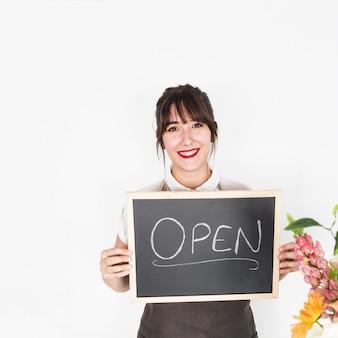 Portrait d'une femme heureuse montrant l'ardoise avec mot ouvert