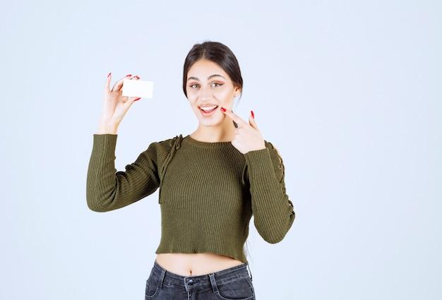 Portrait d'une femme heureuse montrant une carte de visite vierge et pointant vers sa bouche.