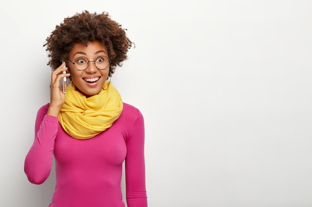 Portrait de femme heureuse à la peau sombre avec une coiffure afro, porte des lunettes, poloneck et écharpe jaune autour du cou, a une expression de visage heureux, des modèles sur un mur de studio blanc