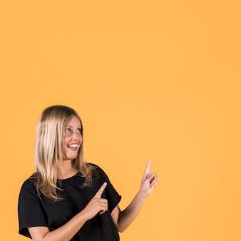 Portrait de femme heureuse pointant vers le haut et levant