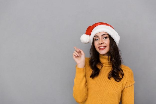 Portrait de femme heureuse portant le chapeau rouge du père noël souriant et pointant le doigt à copyspace, isolé sur fond gris