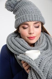 Portrait d'une femme heureuse portant une écharpe et un chapeau avec une tasse de café isolé sur fond blanc